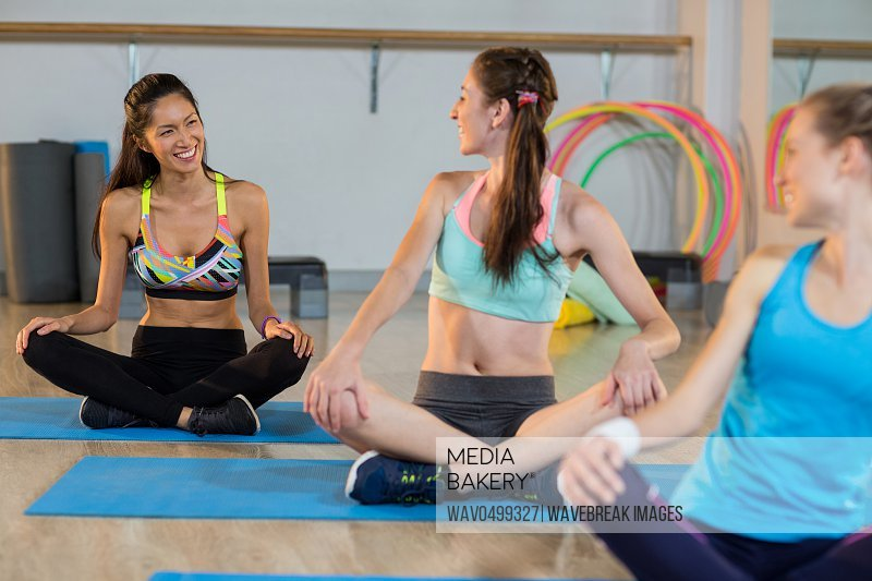 Group of women talking while exercising in gym