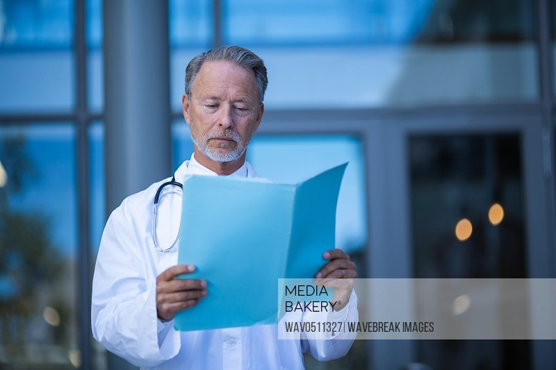 Male surgeon reading medical report at hospital