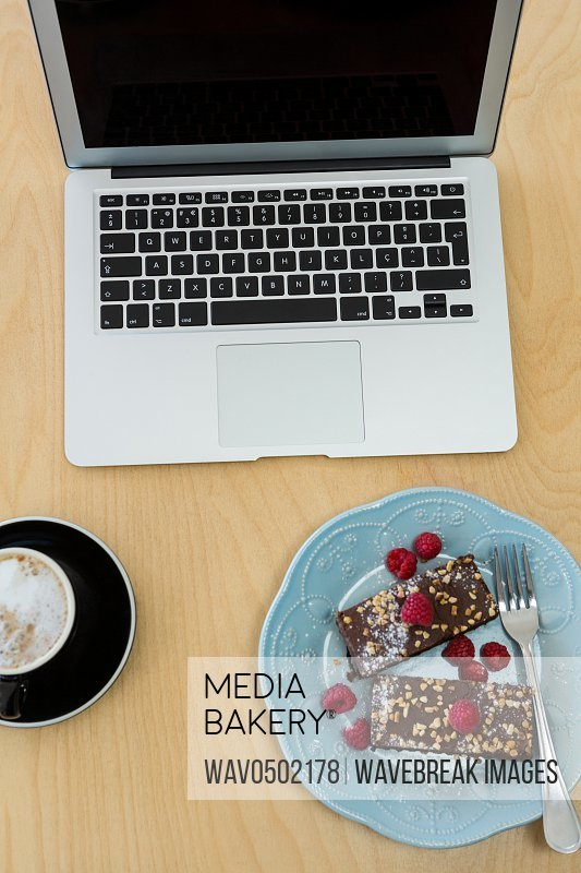 Delicious cakes cup of coffee and laptop on table in cafeteria