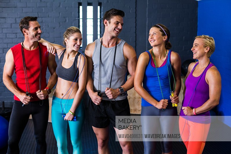 Happy male and female athletes with jump rope standing against wall in gym