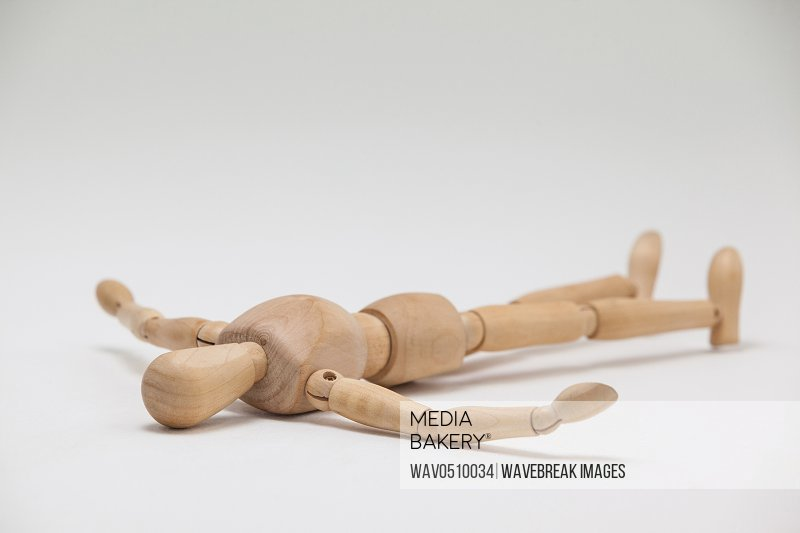 Wooden figurine lying on floor with arms spread against white background
