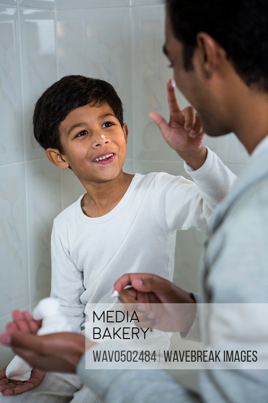 Son applying foam on fathers face in the bathroom at home