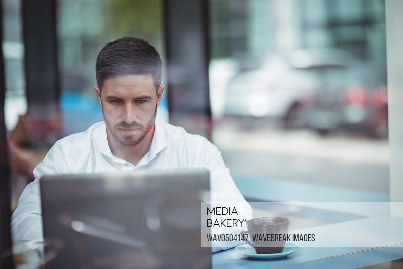 Businessman using laptop while having a cup of coffee in office
