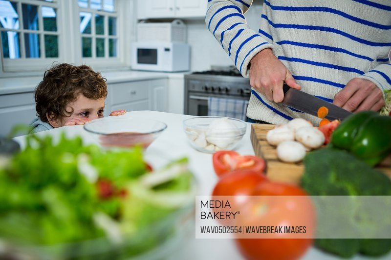 Boy looking while father chopping vegetables in the kitchen