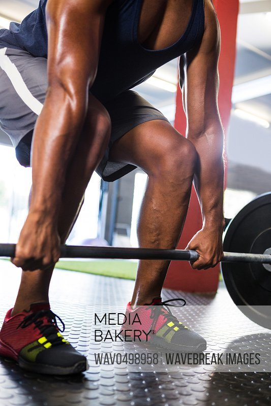 Low section of male athlete lifting barbell in fitness studio