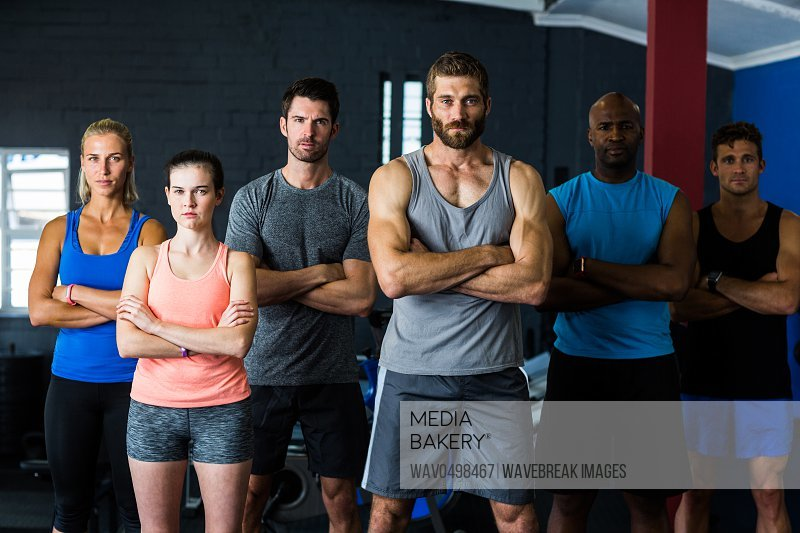 Portrait of serious friends with arms crossed while standing in gym