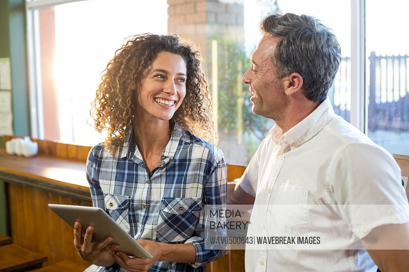 Couple interacting with each other while using digital tablet in supermarket