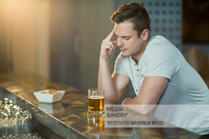 Thoughtful man with glass of whisky sitting at counter in bar