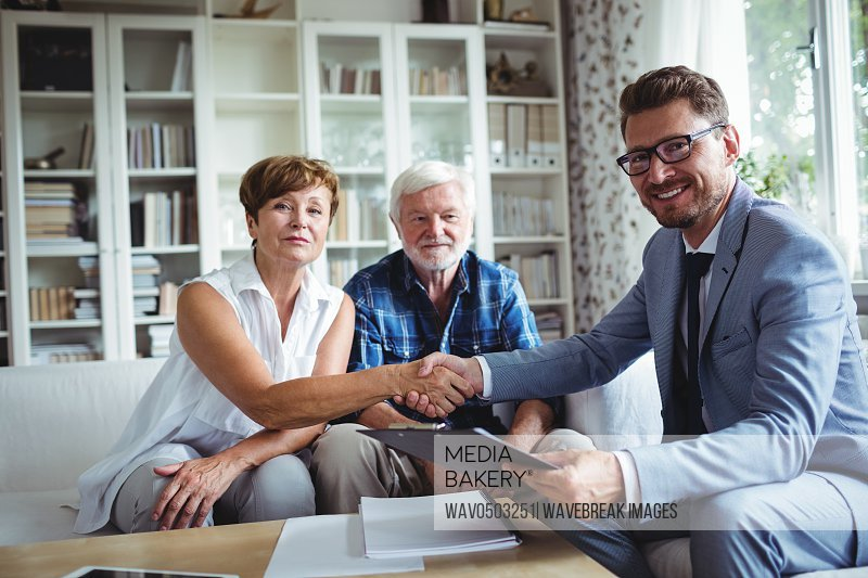 Portrait of financial advisor shaking hands with senior woman in living room