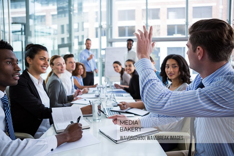 Colleague raising his hand during meeting in office