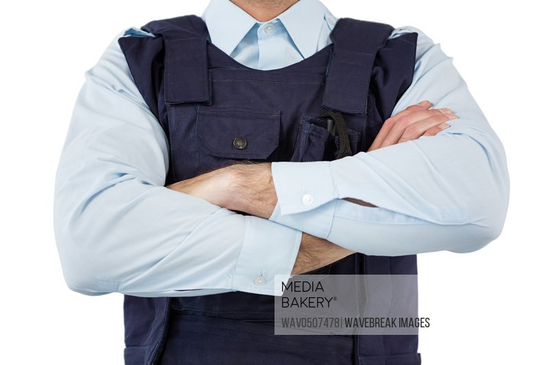 Mid section of security standing with arms crossed against white background