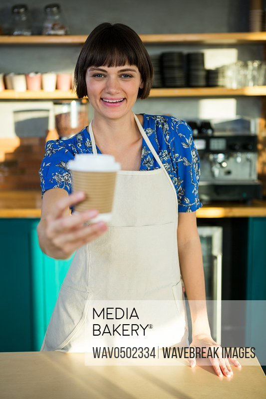 Portrait of smiling waitress offering a cup of coffee in the coffee shop