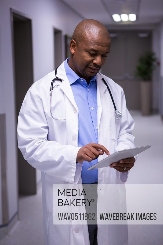 Male doctor standing with digital tablet in corridor at hospital