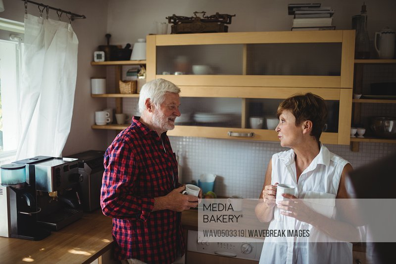 Senior couple interacting while having coffee in kitchen