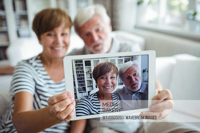 Senior couple clicking a picture on digital tablet in living room