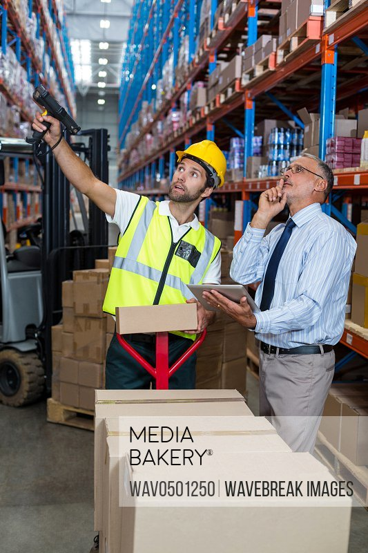 Warehouse manager interacting with male worker in warehouse
