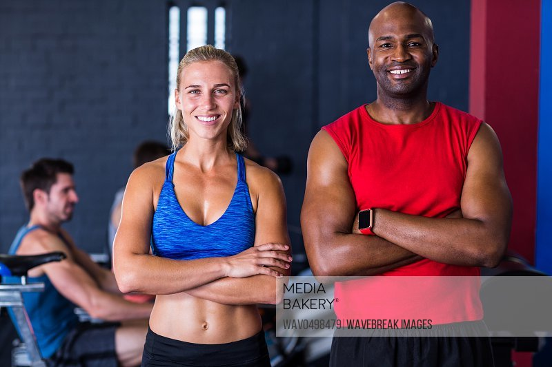 Portrait of smiling friends with arms crossed while standing in gym