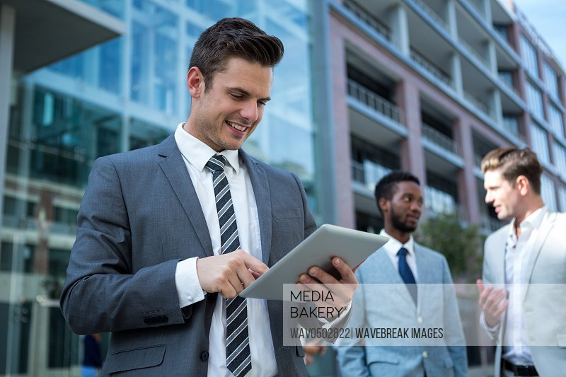 Smiling businessman using digital tablet in the office building