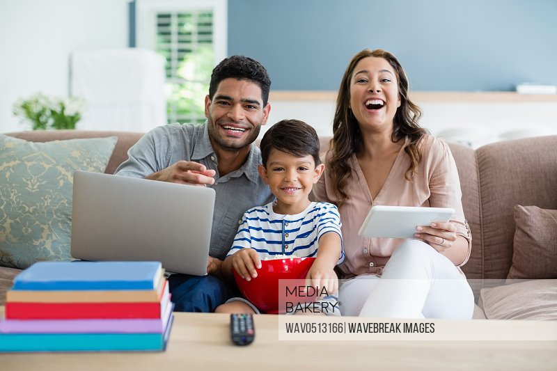 Son watching television while father and mother using laptop and digital tablet at home