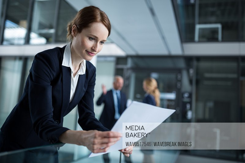 Businesswoman standing in corridor reading document in office