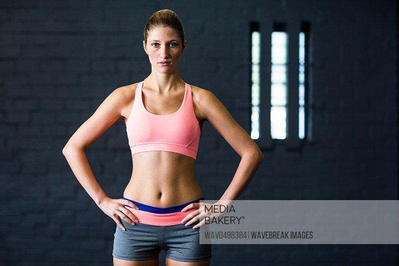 Portrait of fit young woman with hands on hip while standing in gym