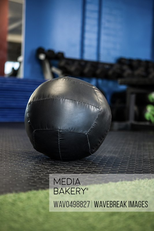Black exercise ball on floor in gym