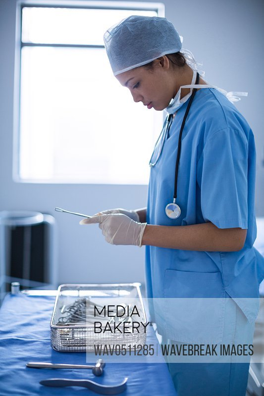 Female surgeon holding surgical equipment at hospital