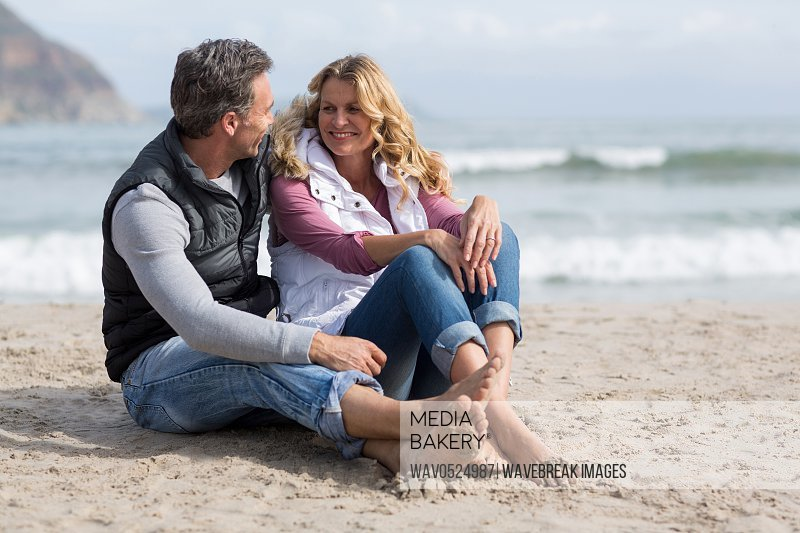 Mature couple sitting together on the beach