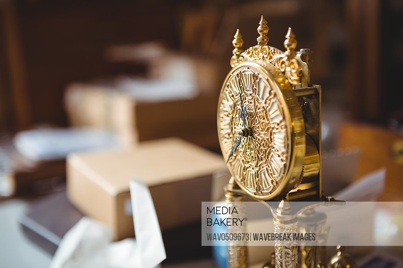 Close-up of golden watch on table in workshop