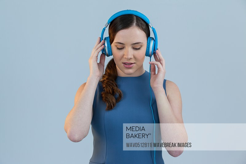 Beautiful woman listening to music on headphones against grey background