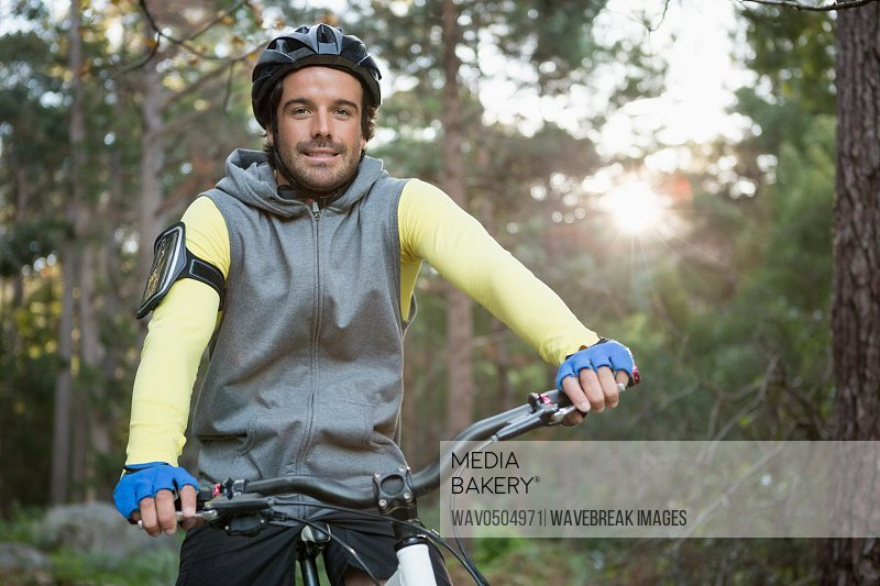 Portrait of male mountain biker riding bicycle in the forest on a sunny day