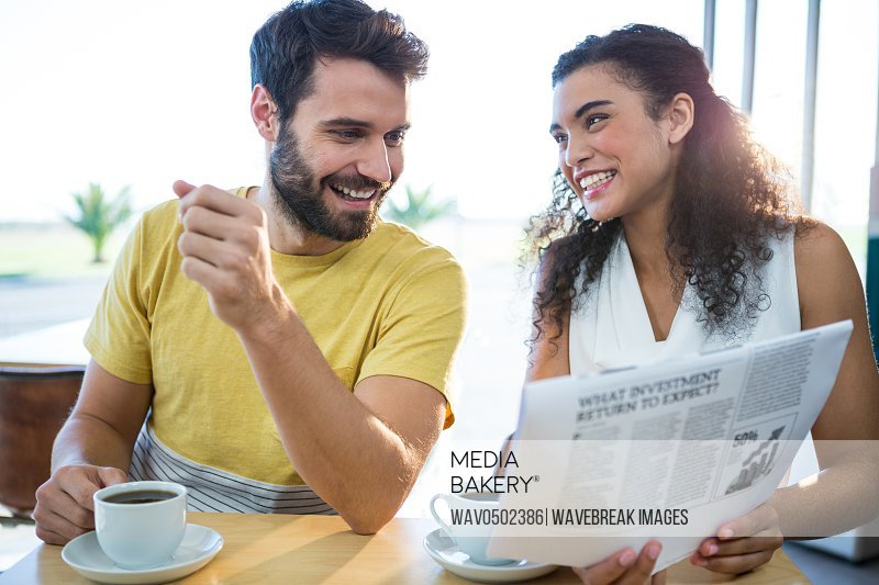Smiling couple reading newspaper while having coffee in coffee shop