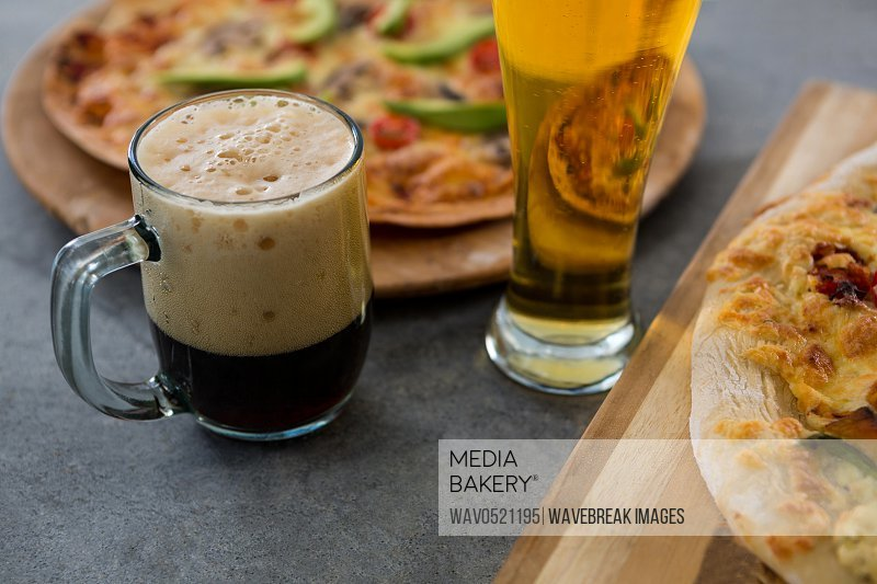 A mug of beer and glass with pizza in the background