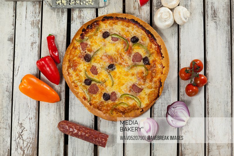 Italian pizza on wooden plank with vegetables and spices