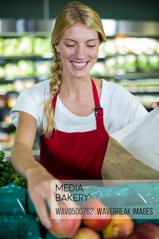 Smiling female staff packing fruits in paper bag at supermarket