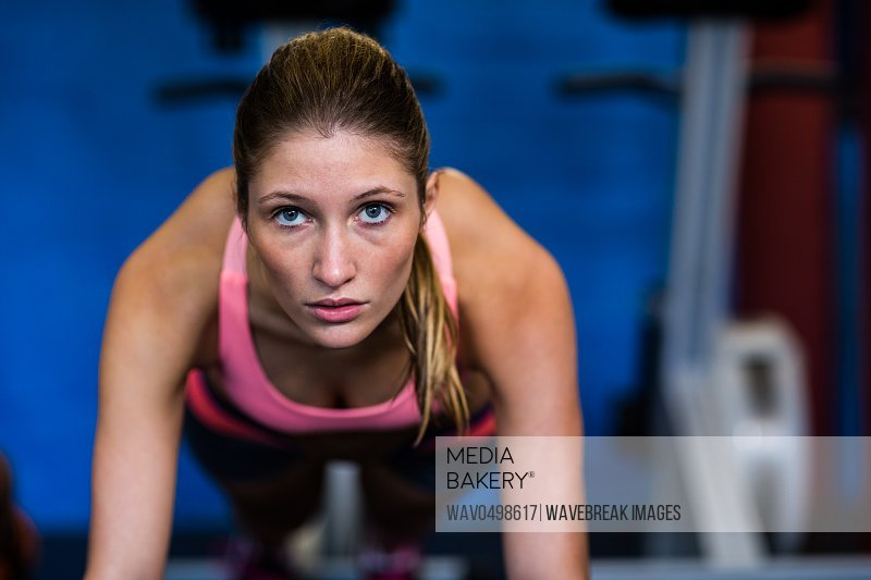 Portrait of determined female athlete doing push-ups in gym