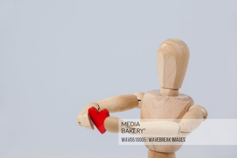 Wooden figurine holding a red heart in front against white background