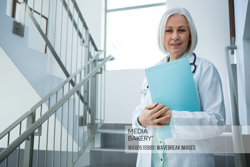 Portrait of doctor standing with file in hospital