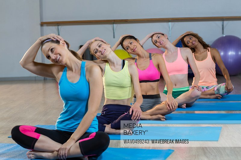 Group of women performing yoga in gym