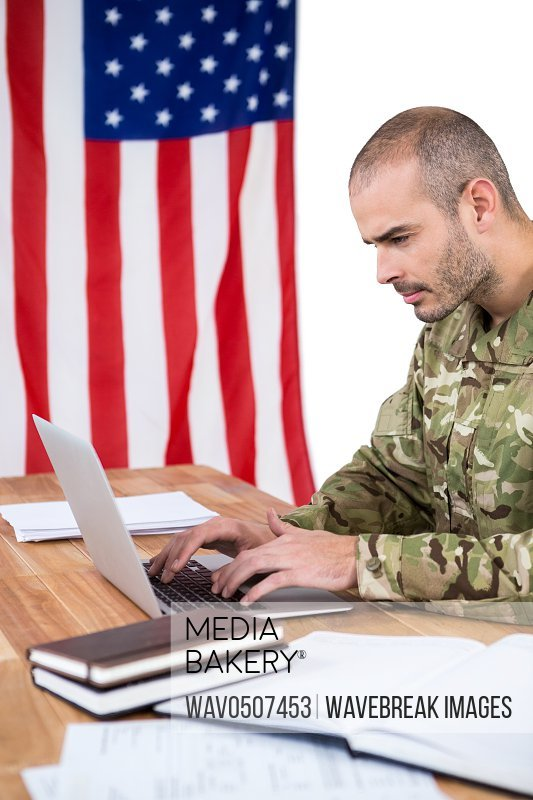 Solider using a laptop at desk against white background