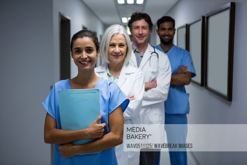 Portrait of smiling surgeons and doctor standing in corridor at hospital