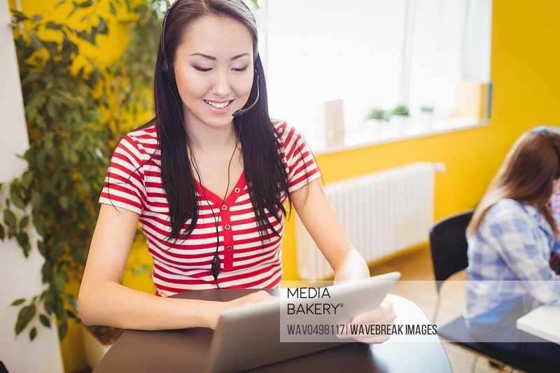 Happy young beautiful female executive using tablet at creative office