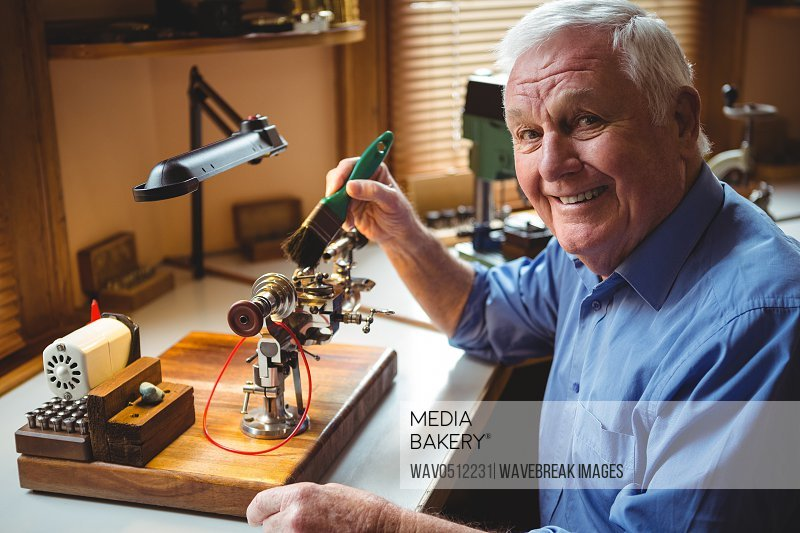 Portrait of horologist repairing a watch in the workshop