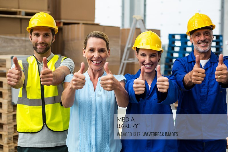 Portrait of warehouse manager and worker showing thumbs up in warehouse