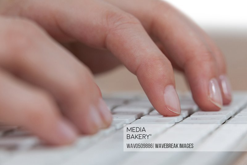 Close-up of businesswoman typing on keyboard