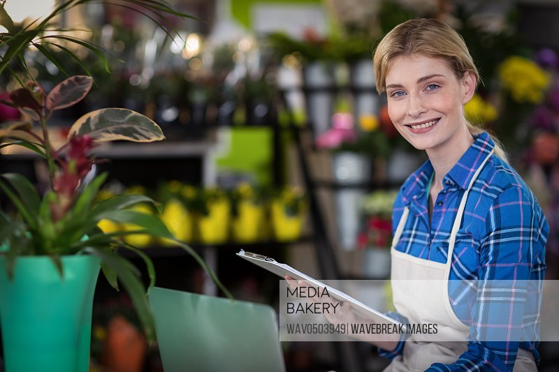 Female florist holding clipboard in the flower shop