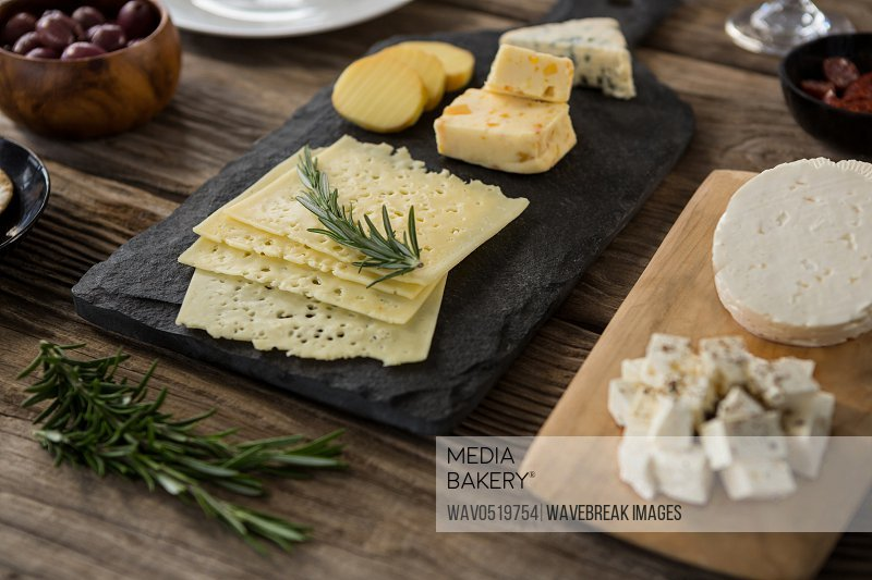 Variety of cheese olives biscuits and rosemary herbs on wooden table