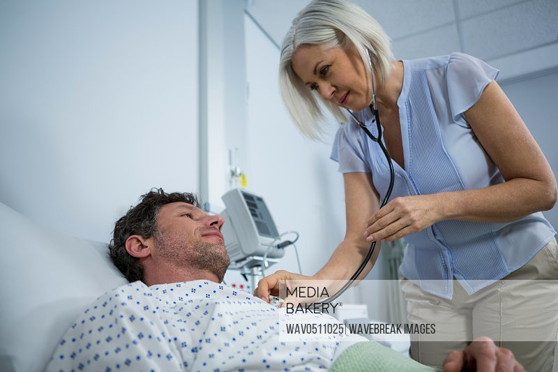 Doctor examining a patient with a stethoscope while checking glucose bottle in hospital