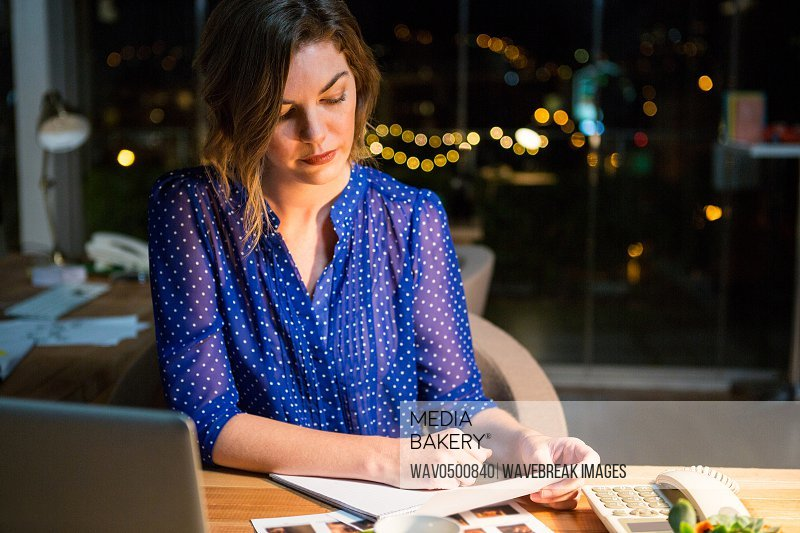 Businesswoman reading document at her desk in the office