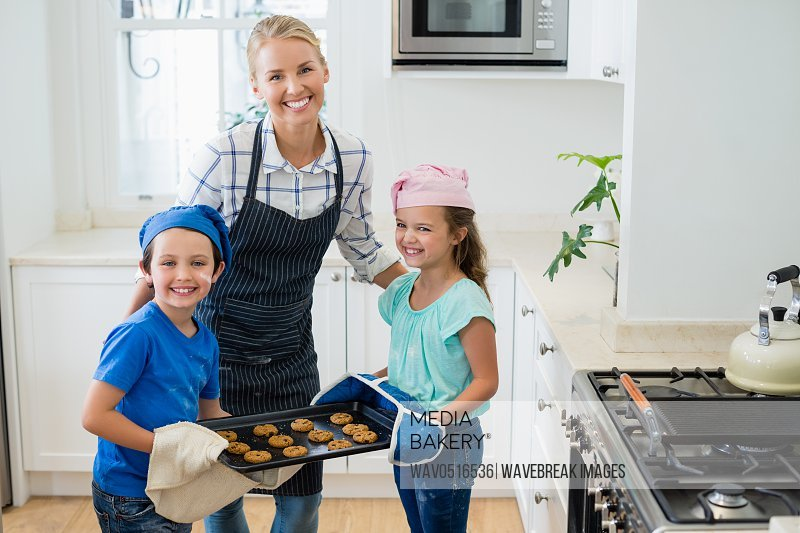 Mother and kids holding tray of baked cookies in kitchen
